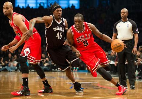 DON EMMERT/ GETTY IMAGES Luol Deng drives past Gerald Wallace Saturday in Game 1 of the Bulls/Nets series in Brooklyn, NY.