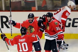 Nam Y. Huh/Associated Press Johnny Oduya (27) celebrates with teammates Michal Rozsival (32) and Patrick Sharp (10) after his go-ahead goal as the Red Wings' Johan Franzen (93) reacts during the third period of Game 1 in Chicago Wednesday.