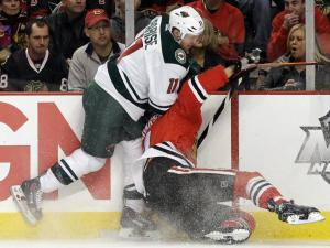Nam Y. Huh/AP  Blackhawks defenseman Niklas Hjalmarsson gets checked into the boards by the Minnesota Wild's Zach Parise during action Saturday at the United Center.