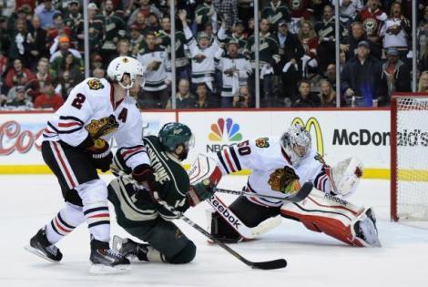 Hannah Foslien/Getty Images Corey Crawford makes one of his 34 saves, helping the Chicago Blackhawks take Game 6, and the series, against Minnesota Tuesday night.