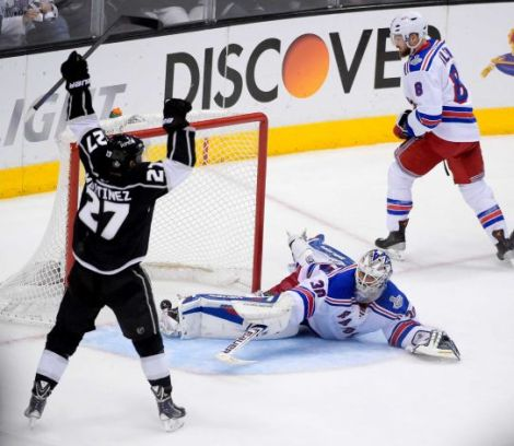 Mark J. Terrill/AP Los Angeles Kings defenseman Alec Martinez, left, celebrates after scoring the winning goal past New York Rangers goalie Henrik Lundqvist during the second overtime period in Game 5 of the Stanley Cup finals, Friday in Los Angeles.