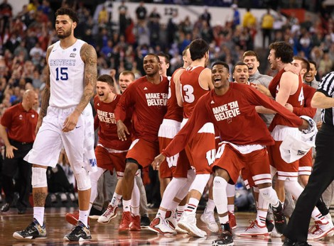 Wisconsin Badgers celebrate as Kentucky Wildcats forward Willie Cauley-Stein (15) walks off the court as they upset Kentucky 71-64 in the 2015 NCAA Men's Division I Championship semi-final game at Lucas Oil Stadium. (USA TODAY Sports)