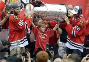 Paul Beaty/AP Patrick Kane (88) and Andrew Shaw (65) help C.J. Reif hold up the Stanley Cup during a rally celebrating the Hawks' Stanley Cup championship, Thursday at Soldier Field. C.J.'s father Clint Reif was the equipment manager for the team and passed away in December 2014.