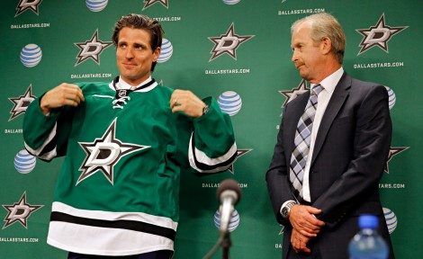 G.J. McCarthy/The Dallas Morning News  New Dallas Stars wing and former Hawk Patrick Sharp (left) dons the team jersey as general manager Jim Nill watches during a press conference Monday, July 20 in Dallas.