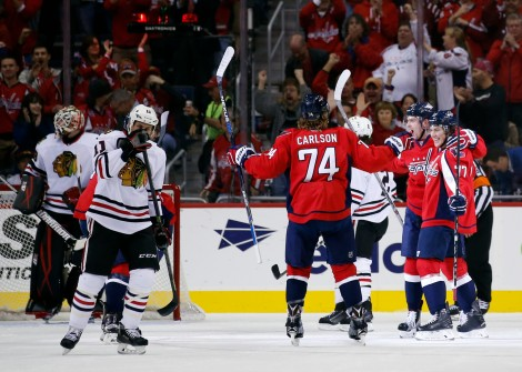 Washington Capitals right wing T.J. Oshie (77), center Evgeny Kuznetsov (92), from Russia, and defenseman John Carlson (74) celebrate Oshie's goal with Chicago Blackhawks center Andrew Desjardins (11) nearby, in the first period of an NHL hockey game, Thursday, Oct. 15, 2015, in Washington. (AP Photo/Alex Brandon)
