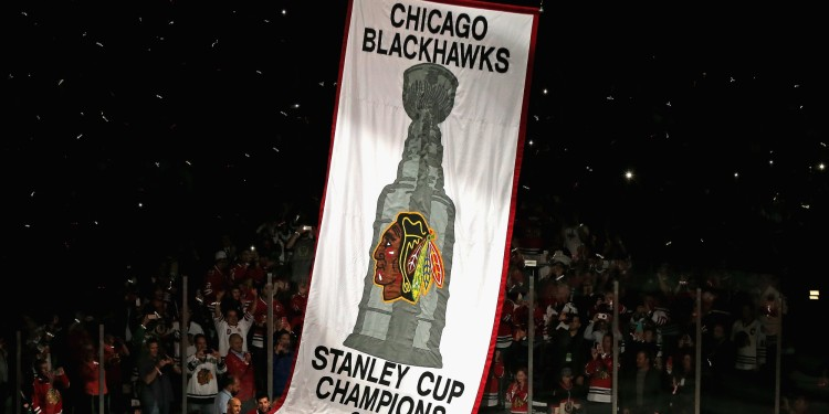CHICAGO, IL - OCTOBER 01: Members of the Chicago Blackhawks watch as the 2013 Stanley Cup Championship banner is hung during a ceremony before taking on the Washington Capitals at the United Center on October 1, 2013 in Chicago, Illinois. (Photo by Jonathan Daniel/Getty Images)